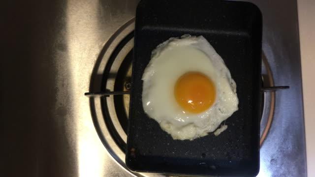 frying egg to make breakfast