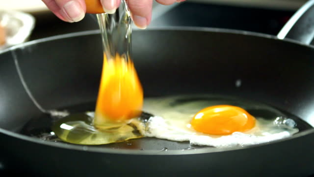 Frying eggs for breakfast slow motion.