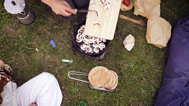 frying mushrooms in a frying pan on a camping trip - east sussex stock videos & royalty-free footage