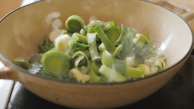 frying off chopped leek for making leek potato soup - potato soup stock videos & royalty-free footage