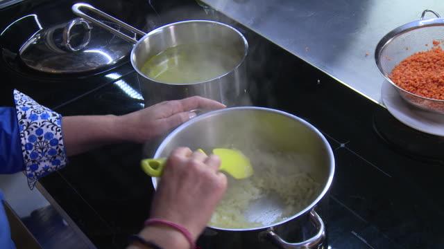 vídeos y material grabado en eventos de stock de frying onions. view of a woman's hand stirring fried onions in a pot. - acero inoxidable