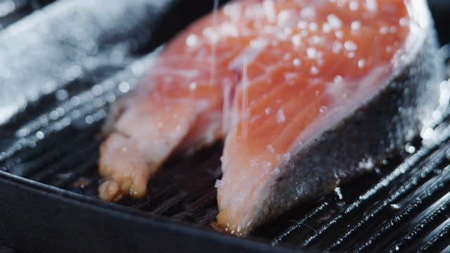 frying salmon on the grill pan. adding salt. extreme close-up - adding salt stock videos & royalty-free footage
