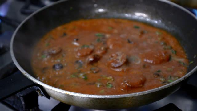 トマトソースにオリーブを添えたソーセージスライスを炒める - フライパン点の映像素材/bロール