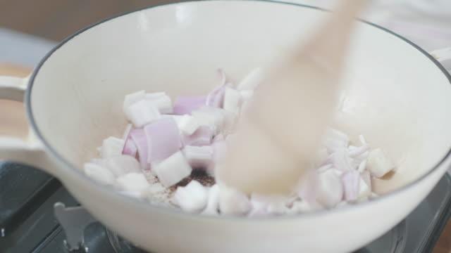 鉄鋳造鍋を調理のエシャロットのタマネギをフライパン - キャンプ用ストーブ点の映像素材/bロール