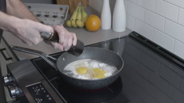 vídeos de stock e filmes b-roll de frying two eggs with pepper for breakfast - saleiro e pimenteiro