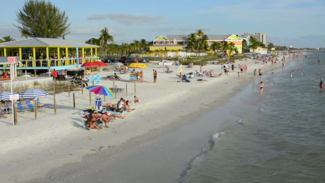 ft myers beach florida beach at famous pier with tourists sand gulf of mexico  restaurants crowded water at beach - fort myers beach stock videos & royalty-free footage
