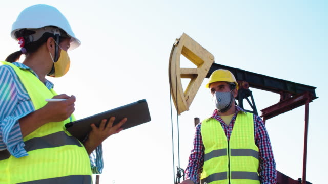 fuel and power generation systems-oil field. maintenance engineers working at a petroleum power station on a bright sunny day. business meeting of two colleagues  wearing protective face masks during the covid-19 pandemic. teamwork. - power equipment stock videos & royalty-free footage