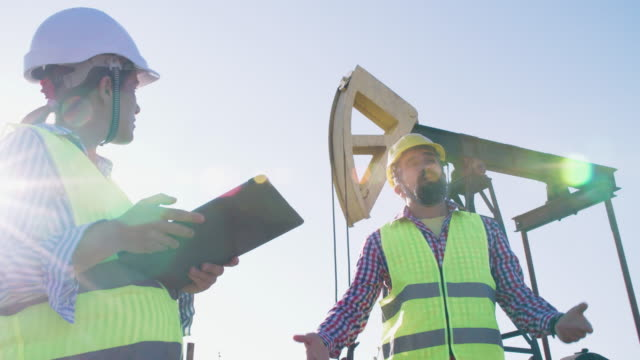 fuel and power generation systems-oil field. maintenance engineers working on the field at a petroleum power station on a bright sunny day. business meeting of two colleagues engineers. teamwork. - power equipment stock videos & royalty-free footage