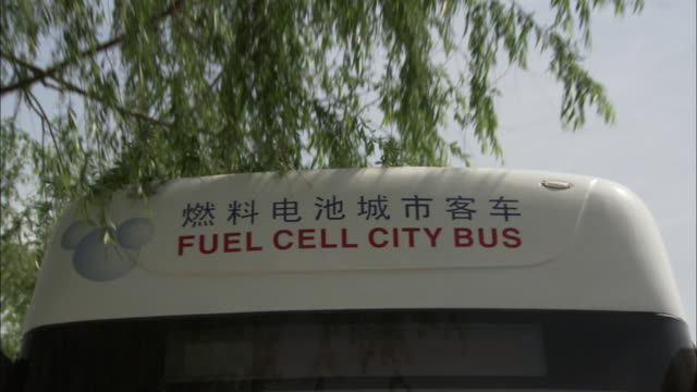 cu la rear pov fuel cell city bus written in english and chinese on top of moving fuel cell bus, beijing, beijing, china - hydrogen stock videos & royalty-free footage