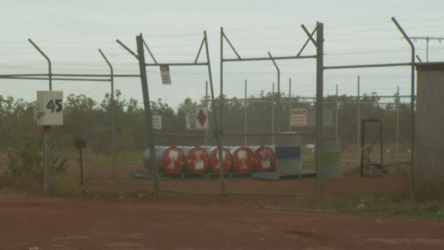 fuel drums behind security fence, australia - fence stock videos and b-roll footage