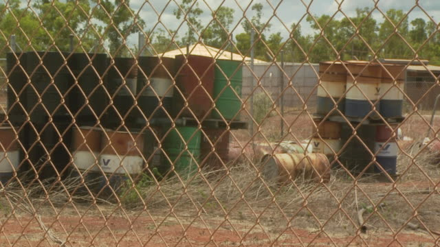 fuel drums behind wire mesh fence.  australia - wire mesh fence stock videos & royalty-free footage