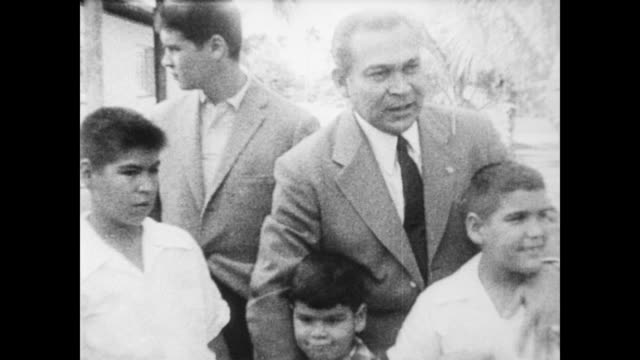 / fulgencio batista poses with family outside residence / members of the media look on. fulgencio batista poses with family on april 10, 1958 in cuba - 1958年点の映像素材/bロール