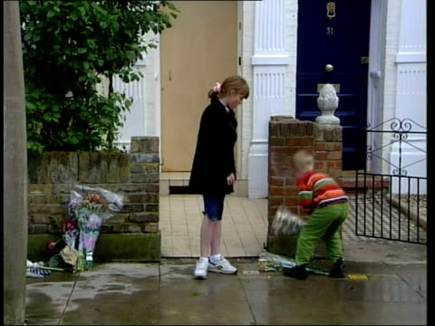 gv little girl boy laying flowers at gate of jill dando's house - jill dando stock videos and b-roll footage