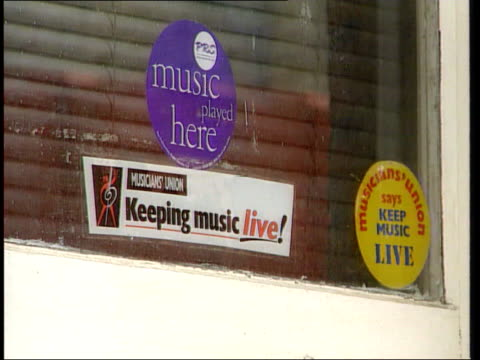 LGV Police officer standing guard outside Barry George's flat MS Police officer outside Barry George's flat CS Three music stickers in window of...