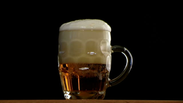 full beer glass with frothy head - empty beer glass stock videos and b-roll footage