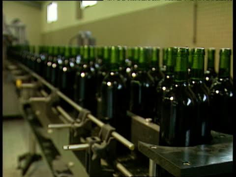 vidéos et rushes de full bottles of red wine move around production line in unison france - chaîne de production