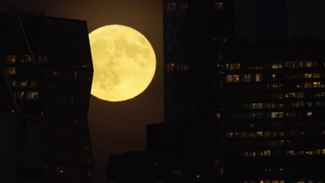 Full bright moon rises behind New York City skyscrapers where people can be seen inside