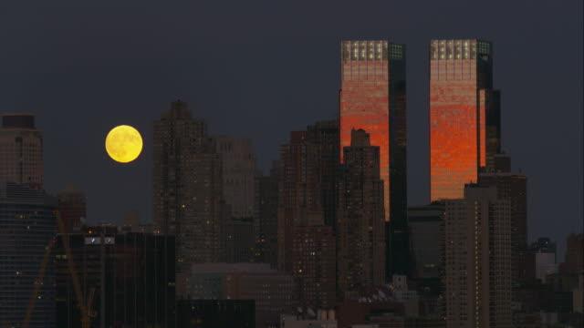 Full, bright, yellow moon slowly rising above New York City skyscrapers