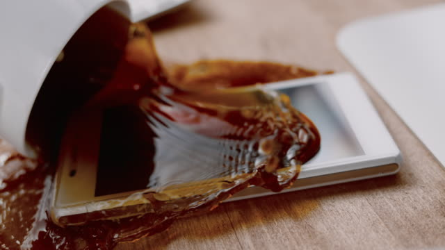 SLO MO LD Full cup of coffee spilling all over a white mobile phone on the desk