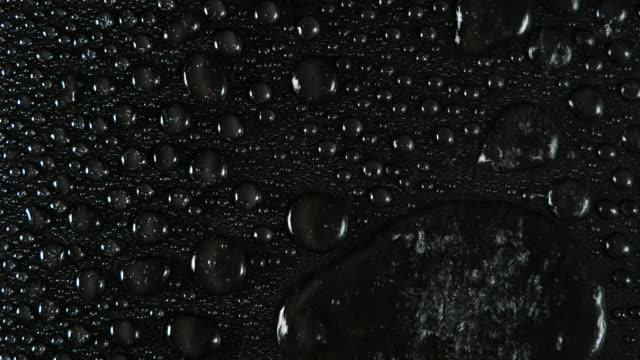 vídeos de stock, filmes e b-roll de full frame of splashes of water drops that fall and slide on a black background. - bolha de replicação