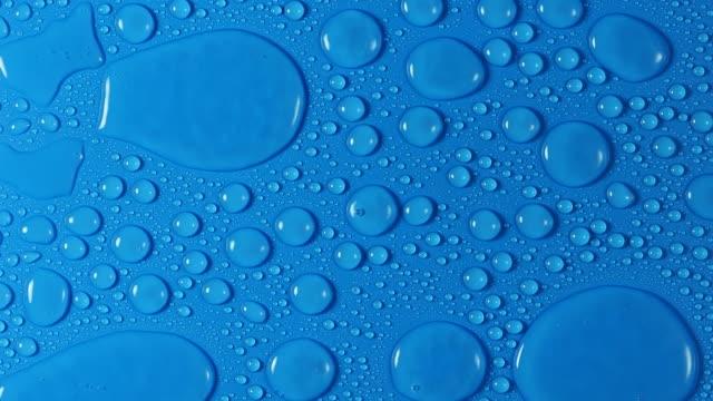 vídeos de stock, filmes e b-roll de full frame of splashes of water drops that fall and slide on a blue background. - bolha de replicação