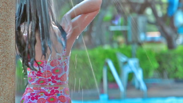 full hd, relaxed arian girl teen in out-door shower on swimming pool. - squirting girl stock videos and b-roll footage