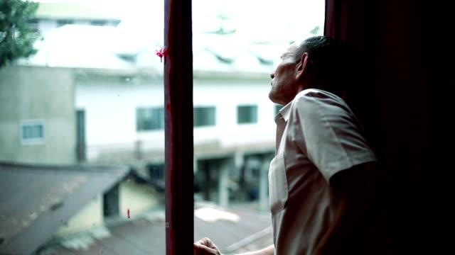 full hd: senior man standing near the window and peeking outside - peeking stock videos & royalty-free footage