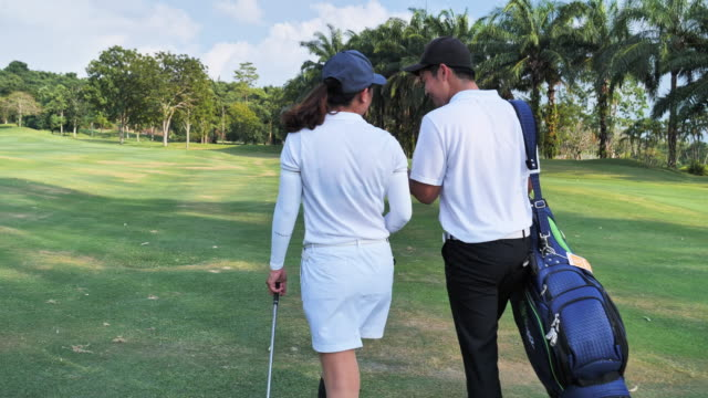 full length of a happy couple with a healthy lifestyle wearing golf outfits, while carrying stand bags with professional clubs towards the golf course in a sunny day of summer - green golf course stock videos & royalty-free footage