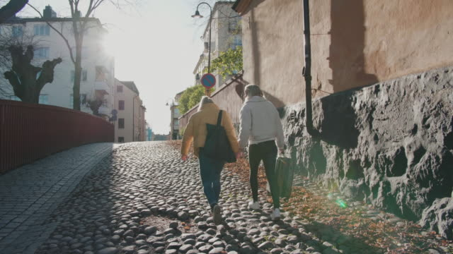 full length of girlfriends holding hands while walking on street in city - stockholm stock-videos und b-roll-filmmaterial