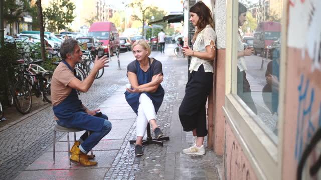 full length of mature male upholstery worker talking while gesturing to female coworkers on footpath in city - kollega bildbanksvideor och videomaterial från bakom kulisserna