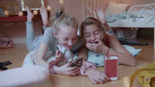 full length of smiling friends using smart phone while lying on floor in bedroom - floor length stock videos & royalty-free footage