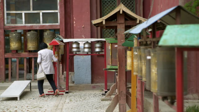 full length of woman rolling prayer wheel at buddhist temple - ulaanbaatar, mongolia - ulan bator stock videos & royalty-free footage
