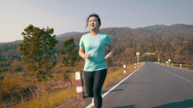 vídeos y material grabado en eventos de stock de duración completa de la mujer corriendo en el camino contra el cielo - corredora de footing