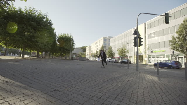 full length of young man in suit skateboarding while throwing paper on footpath in city during sunny day - erfurt, germany - full length bildbanksvideor och videomaterial från bakom kulisserna