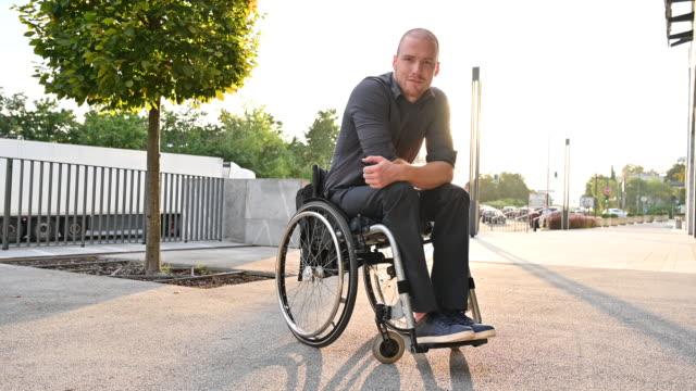 vídeos de stock e filmes b-roll de full length portrait of relaxed young man in wheelchair - cadeira de rodas