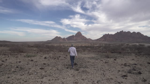 stockvideo's en b-roll-footage met full length rear view of male tourist walking towards mountains against sky, man is on vacation at remote area - spitzkoppe, namibia - groothoek