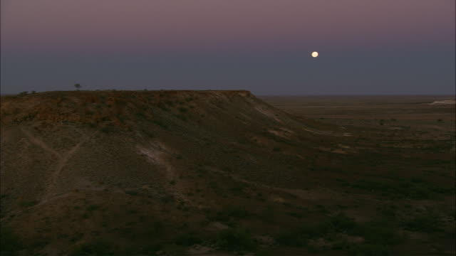 ws pan full moon above plateau  at twilight, coober pedy, south australia, australia - coober pedy stock videos & royalty-free footage