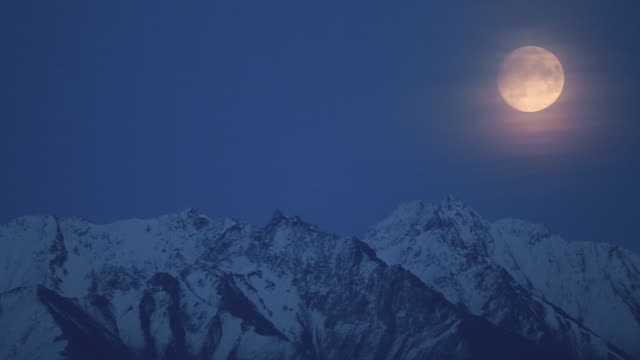 vídeos de stock e filmes b-roll de full moon above the mountains - tempo real
