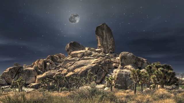 a full moon and stars in a night sky over a giant rock formation. - digital enhancement stock videos and b-roll footage