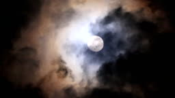 Full moon at night with bright and dark clouds
