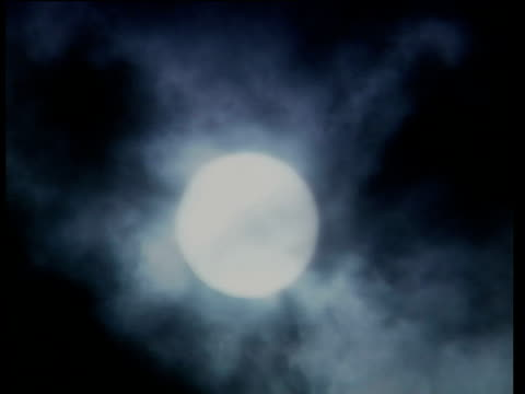 Full moon in dark night sky with clouds rolling past.