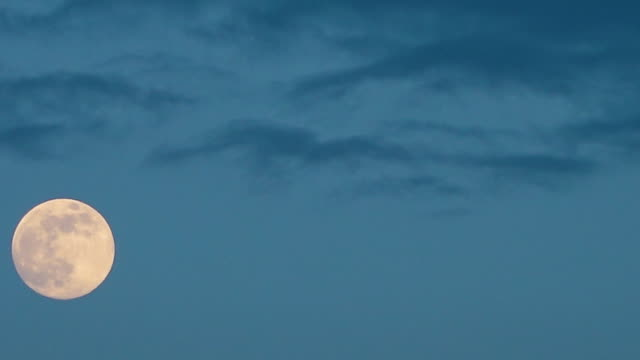 a full moon moves across a dusky cloudy sky - moving up点の映像素材/bロール