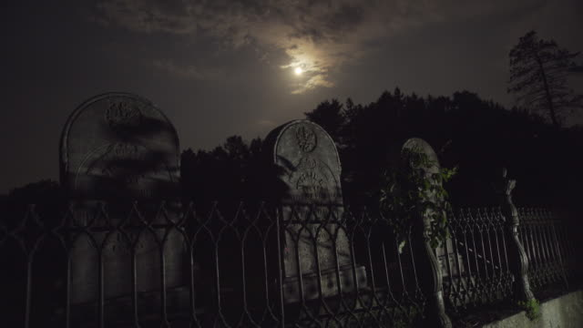 vídeos de stock e filmes b-roll de full moon over tombstones - cemitério