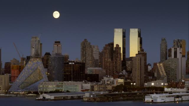 a full moon rises behind the manhattan skyline - ウォーターフロント点の映像素材/bロール