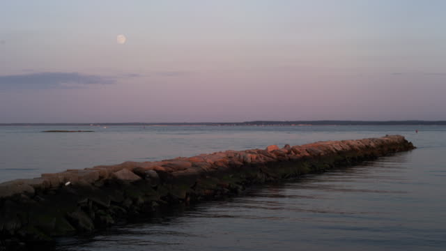 Full moon rises over breakwater and Long Island Sound in timelapse