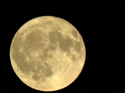 stockvideo's en b-roll-footage met a full moon rises slowly in the night sky. - de ruimte en astronomie