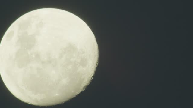 Full moon rises through shot.