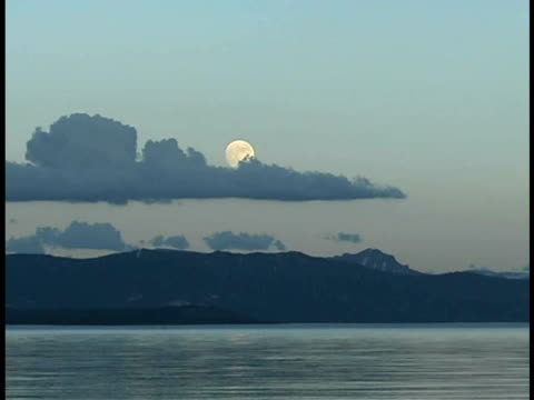 ws, full moon rising above lake and mountains, yellowstone national park, wyoming, usa - lakeshore stock videos & royalty-free footage