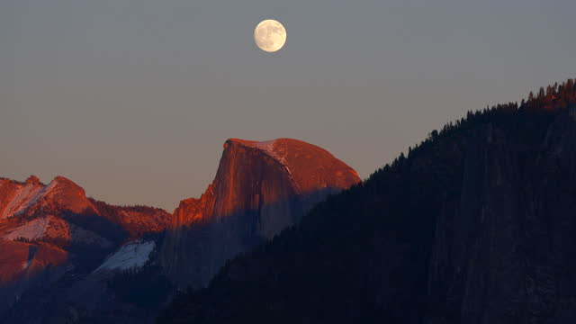 full moon rising at sunset directly over half dome, medium view, yosemite valley, near tunnel view lookout, yosemite national park, california, 4k video - californian sierra nevada stock videos & royalty-free footage