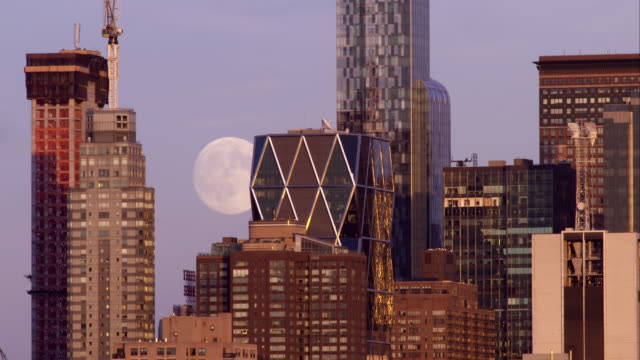 Full moon rising behind abstract looking New York City skyscrapers on a clear night
